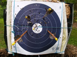 Four fletched arrow and a bareshaft impacting an NFAA target